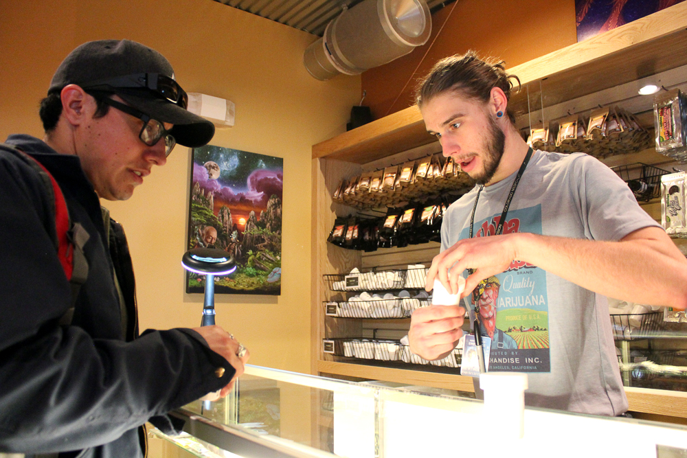 "Kris Knox, right, a bud tender, helps Kris Bunker of Boulder choose a strain of weed at the Terrapin Care Station, Tuesday, Feb. 18, 2014, in Boulder, Colo. The Terrapin Care Station, located at the corner of Folsom Street and Canyon Boulevard, was the first recreational pot shop to open in the city of Boulder. ""Dispensaries out [in California] are getting closed like crazy, but here is awesome. A lot of people from California are probably going to come out here,"" said Bunker, who recently moved from California. (Kai Casey/CU Independent)"